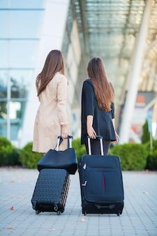 Vacanza. due eleganti viaggiatori donne che camminano con i loro bagagli in aeroporto