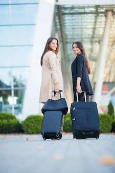 Vacanza. due ragazze felici che viaggiano insieme all'estero, portando i bagagli in valigia in aeroporto