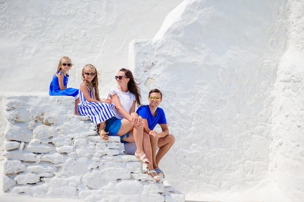 Vacanza in famiglia in europa. genitori e figli in strada del tipico villaggio tradizionale greco con pareti bianche e porte colorate sull'isola di mykonos, in grecia