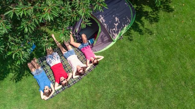 Vacanza in famiglia nella vista aerea dall'alto del campeggio dall'alto, genitori e figli si rilassano e si divertono nel parco, tenda e attrezzatura da campeggio sotto l'albero, concetto di famiglia in campo all'aperto