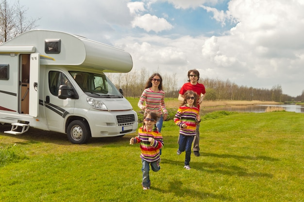 Vacanza in famiglia, viaggio in camper con bambini, genitori felici con bambini in viaggio di vacanza in camper, camper esterno
