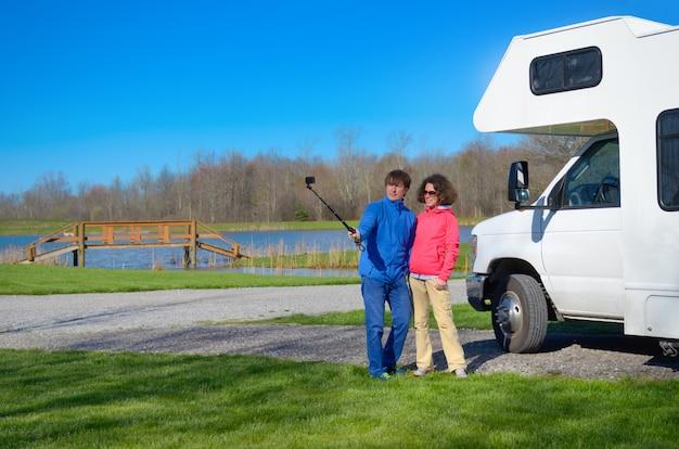 Vacanza in famiglia, viaggio in camper, coppia felice facendo selfie di fronte camper in viaggio di vacanza in camper