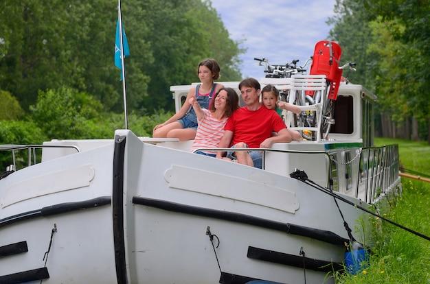 Vacanza in famiglia, viaggio su chiatta nel canale, genitori felici con bambini che si divertono in crociera sul fiume in casa galleggiante