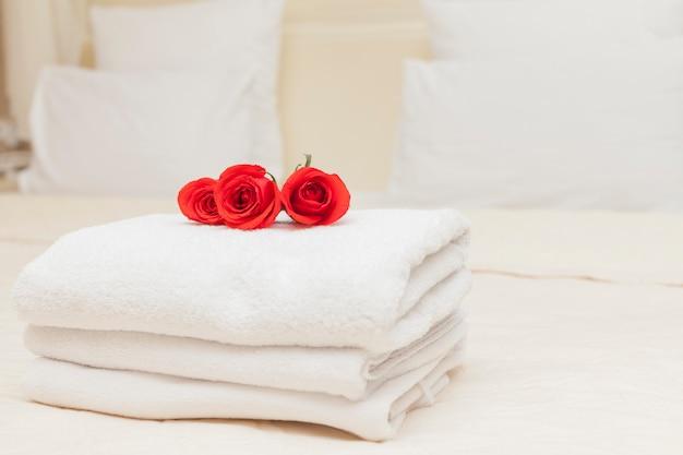 Vacanza romantica con rose rosse su asciugamani bianchi