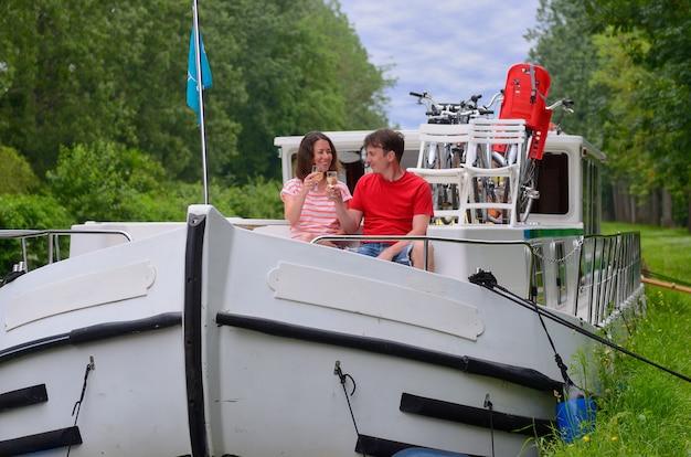 Vacanza romantica, viaggio sulla chiatta nel canale, coppia felice divertirsi in crociera sul fiume in casa galleggiante