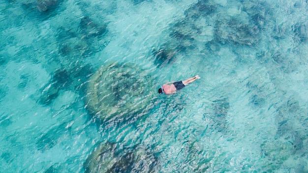 Vacanza turistica snorkeling uomo nuoto snorkeling in paradiso acque limpide. nuota lo snorkeler del ragazzo in acque cristalline e barriere coralline. sfondo oceano turchese.