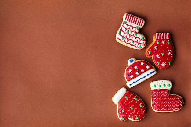 Vacanze di capodanno, biscotti di panpepato rossi e coni sul tavolo rosso scuro. copia spazio.