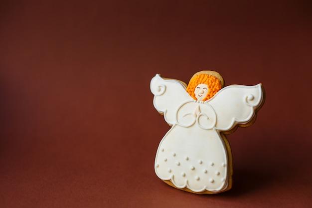 Vacanze di capodanno, biscotto di pan di zenzero di angelo su copyspace rosso scuro.