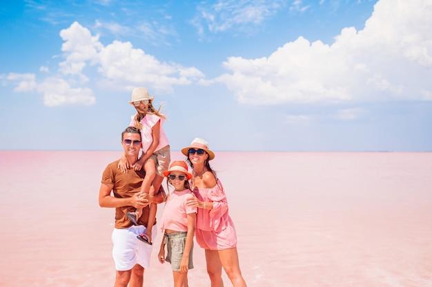 Vacanze di famiglia. genitori felici con due bambini su un lago salato rosa. bellissima natura e paesaggio straordinario
