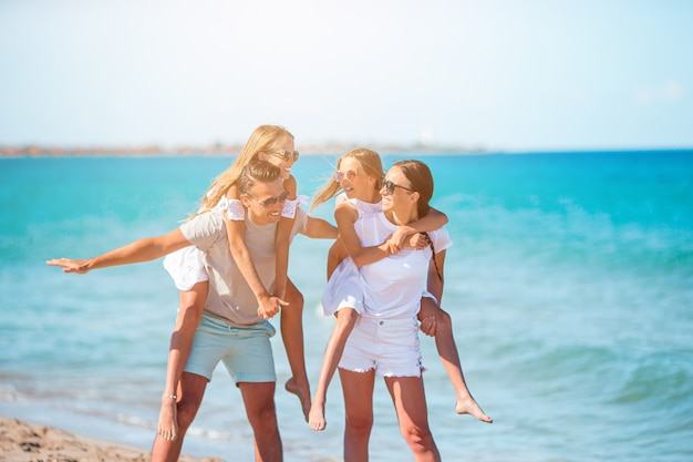 Vacanze di famiglia. i genitori con bambini in spiaggia si divertono insieme