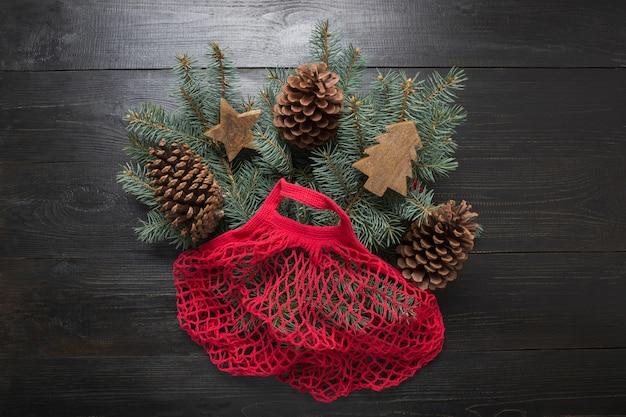 Vacanze di natale a zero rifiuti. rami di conifere in eco sacchetto di cotone rosso su tavola nera. natale ecologico.