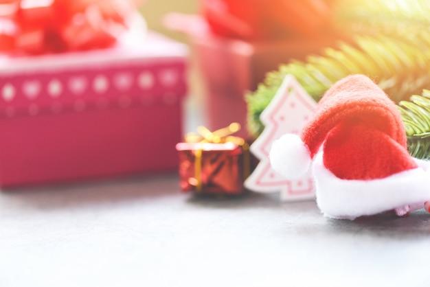 Vacanze di natale con confezione regalo decorazione cappello di babbo natale e rami di abete