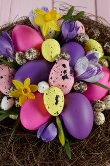 Vacanze di pasqua. grande nido con uova di pasqua multicolori, croco lilla e fiori gialli del narciso su una superficie di legno rosa