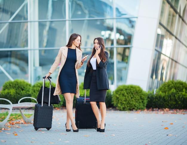 Vacanze, due ragazze felici che viaggiano insieme all'estero, portando bagagli in valigia in aeroporto