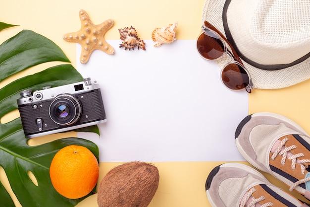 Vacanze estive. carta bianca, foglia di monstera, fotocamera retrò, scarpe da ginnastica, occhiali da sole e frutti esotici su sfondo giallo