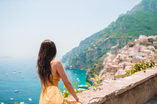 Vacanze estive in italia, giovane donna nel villaggio di positano sullo sfondo, costiera amalfitana, italia