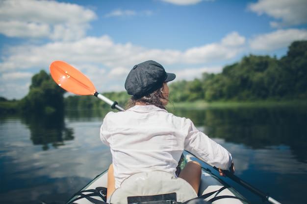 Vacanze estive - vista posteriore della giovane donna in kayak sul fiume.