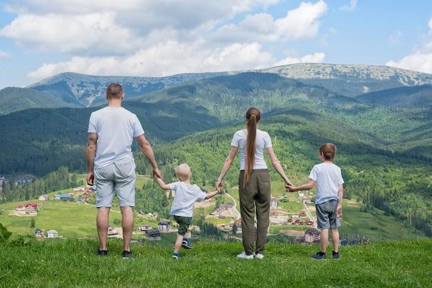 Vacanze in famiglia. genitori e due figli ammirano la vista sulla valle. montagne in lontananza. vista posteriore