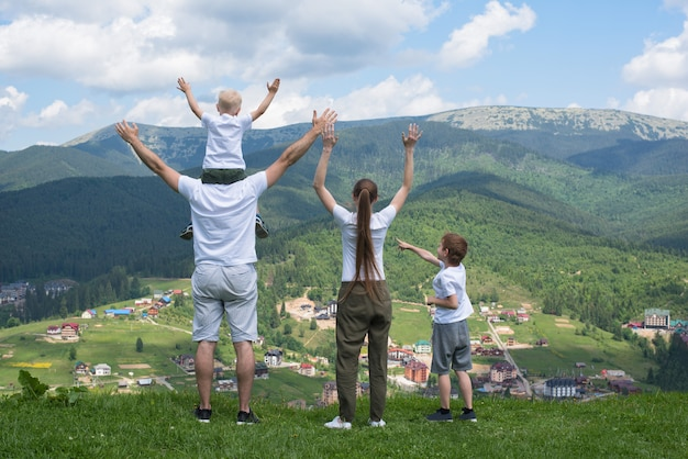Vacanze in famiglia. genitori e figli stanno con le mani in alto. montagne sullo sfondo. vista posteriore.