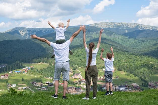 Vacanze in famiglia. genitori e figli stanno con le mani in alto.