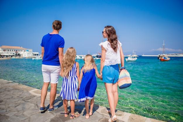 Vacanze in famiglia in europa. genitori e bambini che esaminano la vecchia città chora nell'isola di mykonos, grecia