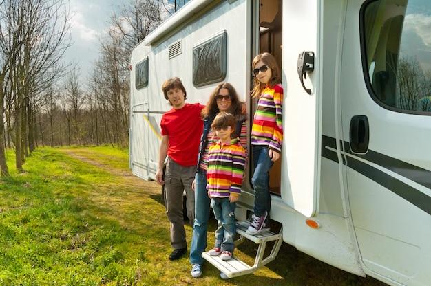 Vacanze in famiglia, viaggi in camper con bambini, genitori felici con bambini in viaggio di vacanza in camper