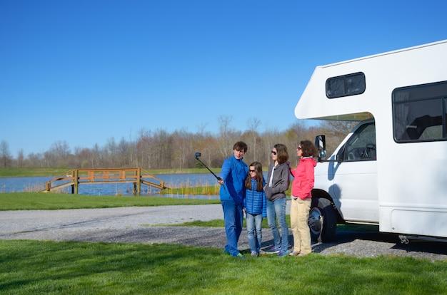 Vacanze in famiglia, viaggi in camper con bambini, genitori felici con bambini si divertono e fanno selfie in viaggio di vacanza in camper, camper esterno