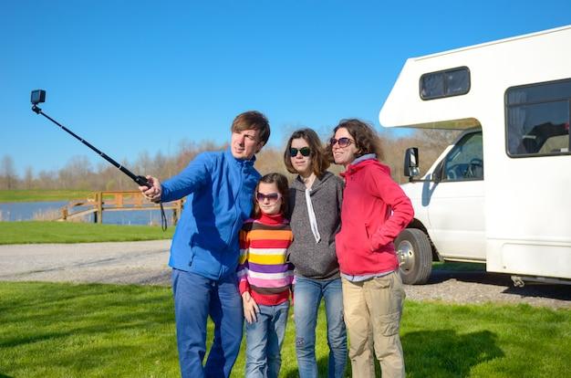 Vacanze in famiglia, viaggi in camper con bambini, genitori felici con bambini si divertono e fanno selfie in viaggio di vacanza in camper