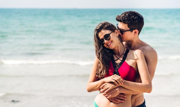 Vacanze romantiche amanti giovani coppie felici abbraccio e in piedi sulla sabbia in mare divertendosi e rilassarsi insieme sulla spiaggia tropicale. vacanze estive