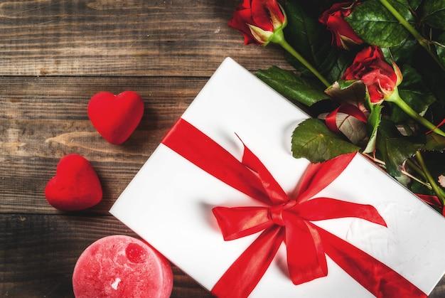 Vacanze, san valentino. bouquet di rose rosse, cravatta con un nastro rosso, con confezione regalo incartata. sul tavolo di legno, copyspace vista dall'alto