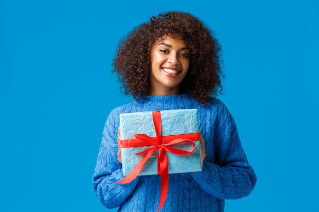 Vacanze, stagione invernale e concetto di natale. bella donna afro-americana carina