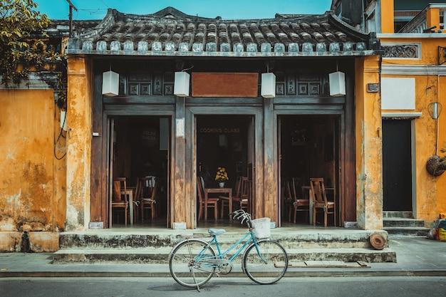 Vada in bicicletta all'ingresso di un caffè nella città vecchia di hoi an, vietnam.