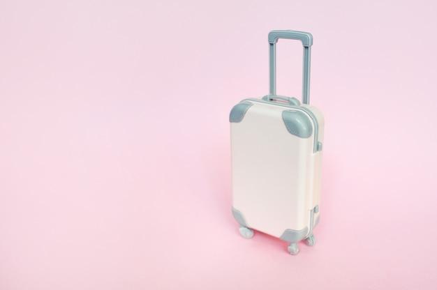 Valigia alla moda sulla vista rosa e superiore con copyspace. concetto di viaggio