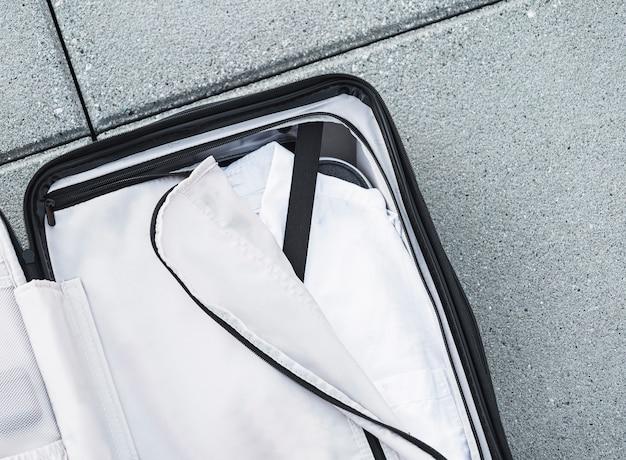 Valigia aperta con camicia bianca