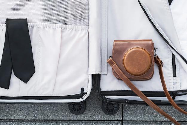 Valigia aperta con custodia in pelle della fotocamera