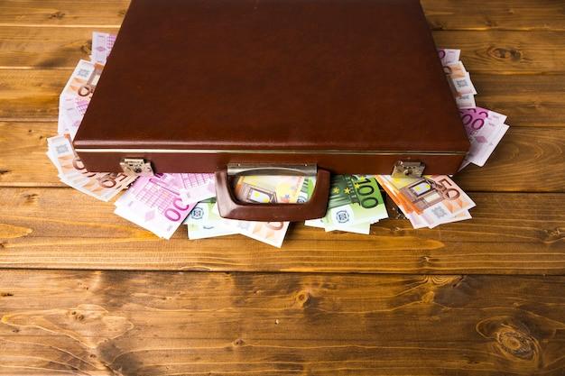 Valigia chiusa ad alto angolo con soldi