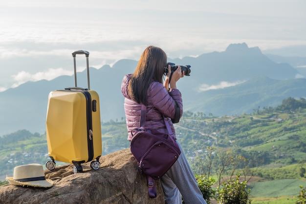 Valigia da viaggio, zaino, le donne scattare una foto con la fotocamera dslr sulla montagna