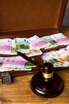 Valigia del primo piano con soldi e martelletto del giudice