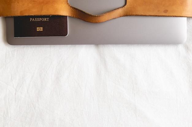 Valigia di cuoio con passaporto e computer portatile nel concetto di viaggio d'affari.