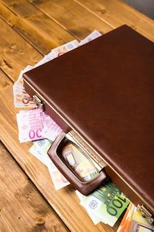 Valigia di legno del primo piano con soldi dentro