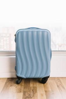 Valigia di viaggio blu vicino alla finestra sul pavimento di legno