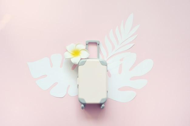 Valigia di viaggio rosa su sfondo rosa con foglie tropicali e fiori bianchi