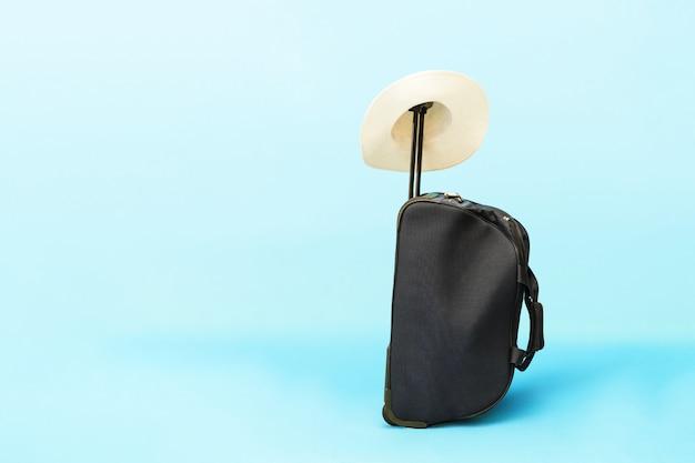 Valigia e cappello su sfondo blu.