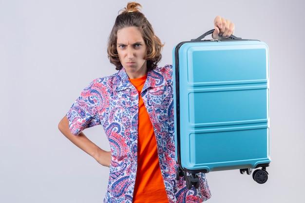 Valigia giovane dispiaciuta della tenuta del tipo del viaggiatore dispiaciuto sulla spalla che esamina macchina fotografica che aggrotta le sopracciglia con la condizione di rabbia