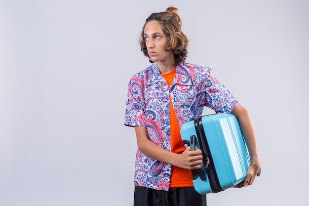 Valigia giovane dispiaciuta della tenuta del tipo del viaggiatore dispiaciuto sulla spalla che guarda da parte con l'espressione triste sulla condizione del fronte