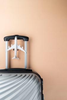 Valigia grigia laica piatta con mini aereo su sfondo pastello.