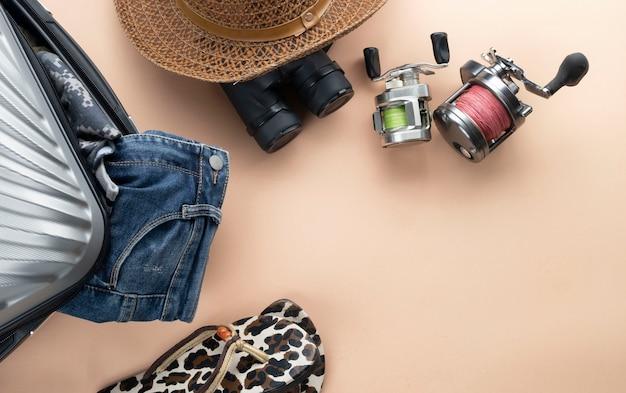 Valigia grigia piatta con binocoli, cappello, jeans, spinning per la pesca e sandali. concetto di viaggio