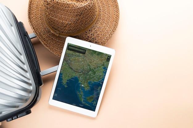 Valigia grigia piatta con cappello marrone e mappa su gadget