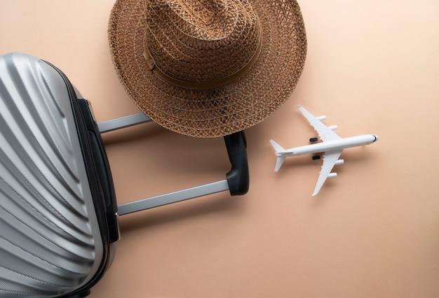 Valigia grigia piatta con cappello marrone e mini aereo