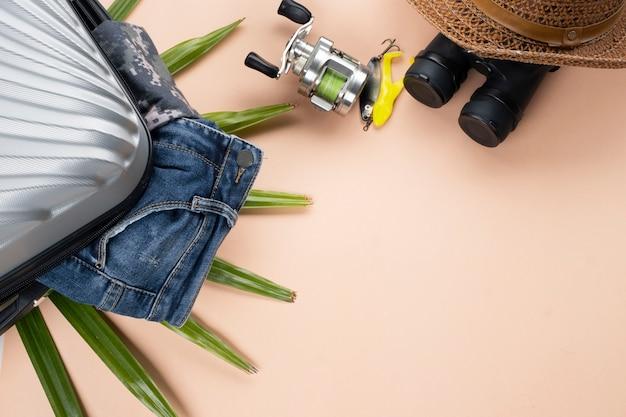 Valigia grigia piatta con jeans, filatura di attrezzi da pesca